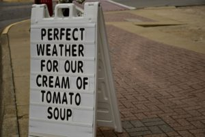 perfect weather for our cream of tomato soup text on brown brick pavement